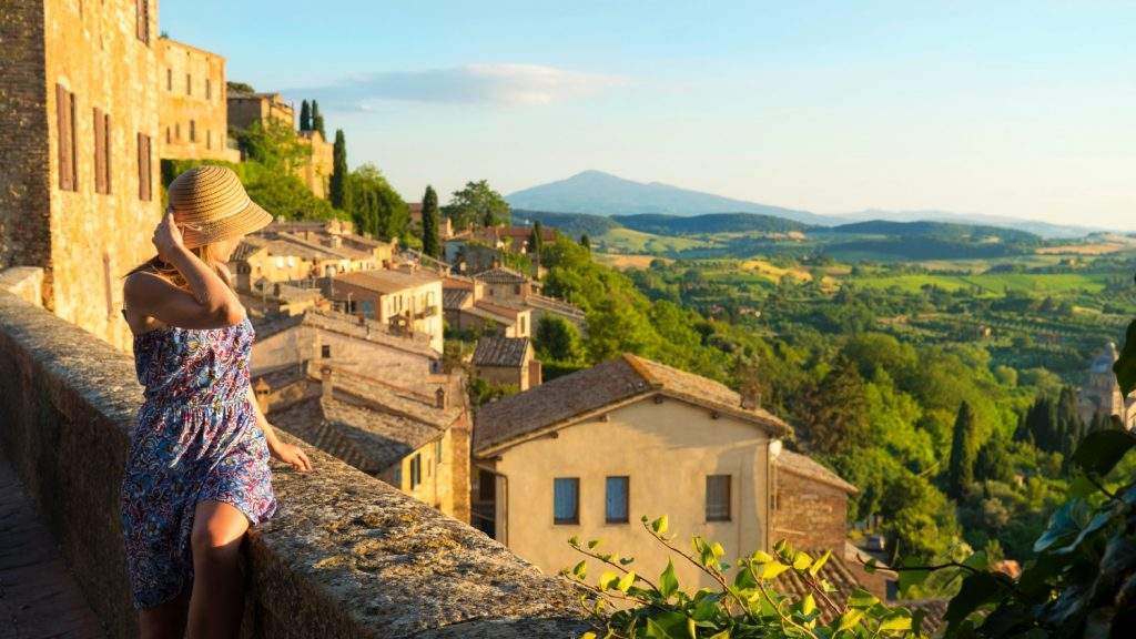 Woman sitting on a stone wall gazing at a Tuscan Medieval Village | Best Time to visit Tuscany