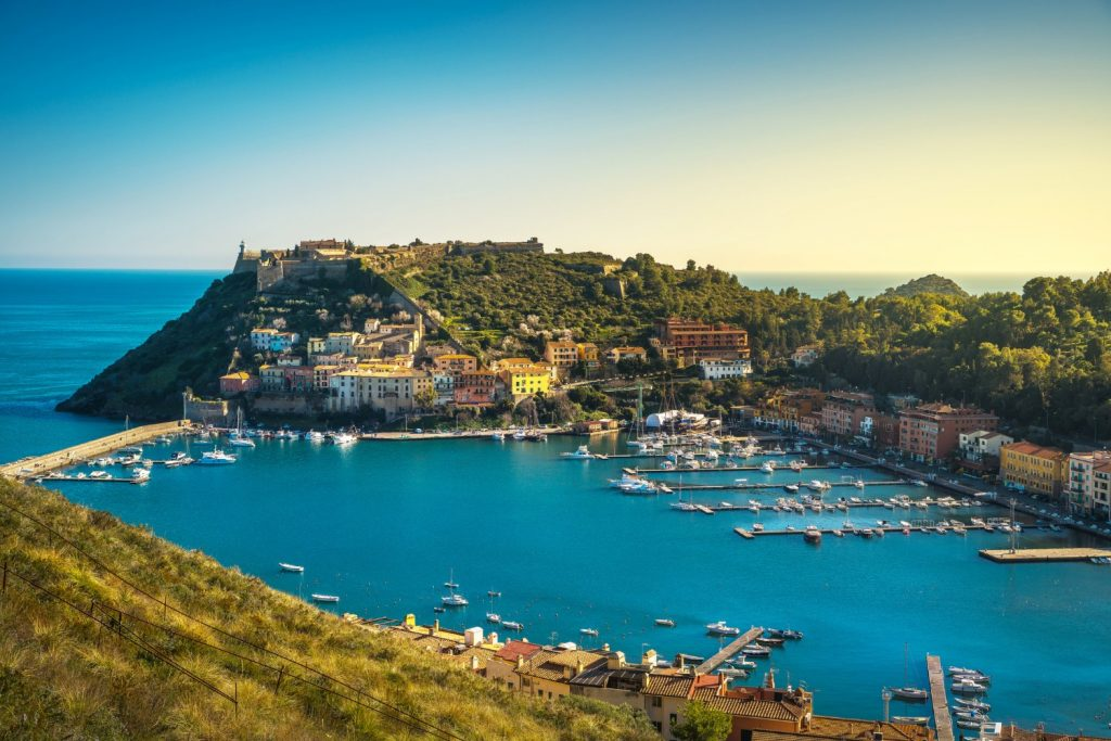 Porto Ercole village and boats in harbor in a sea bay. Aerial view